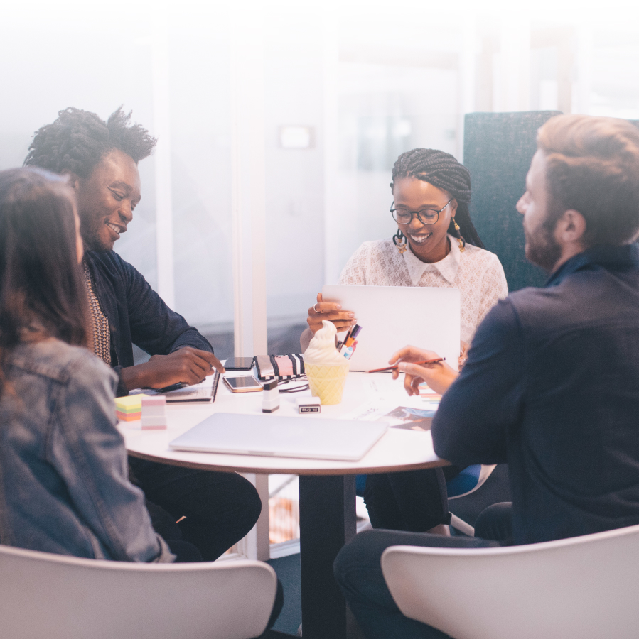 Employees and business owners meeting at a table.